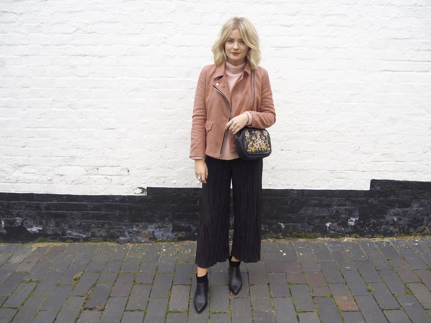 fashion blogger, pleated trousers, pink suede biker jacket, how to wear pink, black pointed boots, embroidered bag, blonde wavy hair, blonde bob,